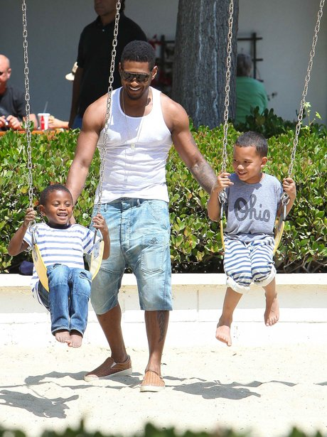 Usher pushing his children on swings