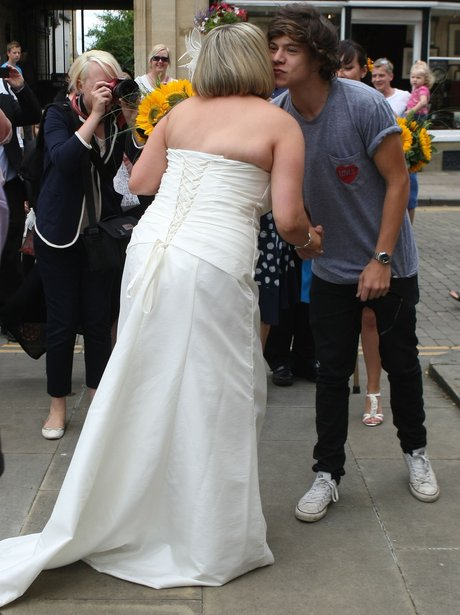 Harry Styles kisses a newylwed on the cheek.