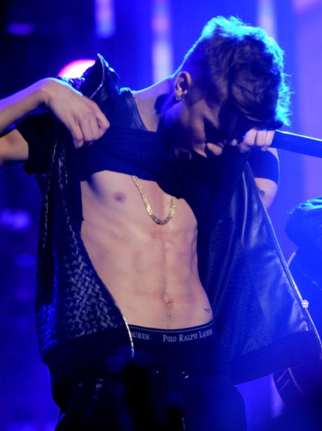 Justin Bieber flashes his abbs on stage
