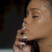 Image 7: Rihanna holding her hand to her face.