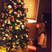Image 8: Taylor Swift sitting next to her Christmas tree