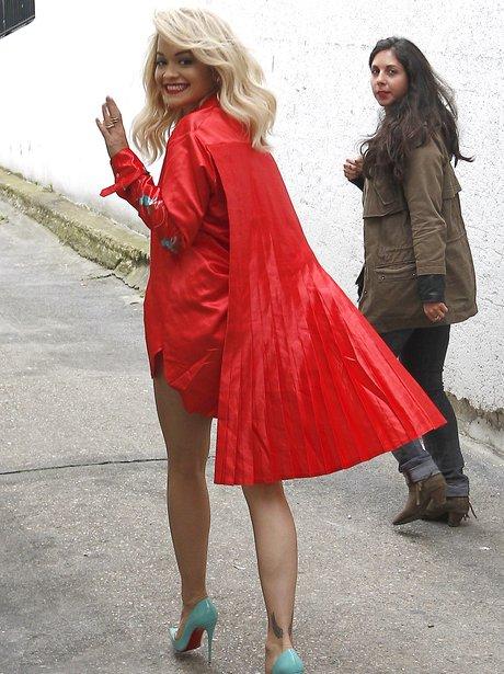 Rita Ora wearing a red cape
