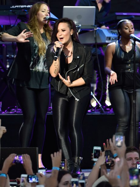 Demi Lovato wearing a black catsuit on stage