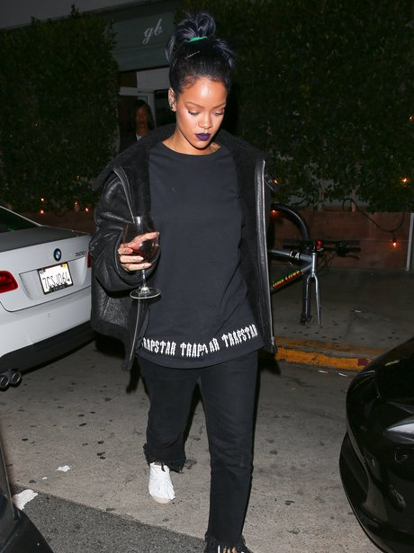 Rihanna carrying wine out of restaurant
