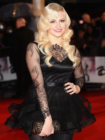 Pixie Lott on the red carpet wearing a stunning black dress