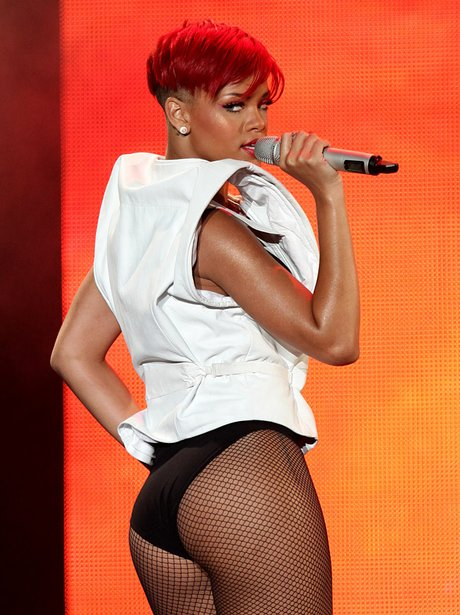 Rihanna performing live on stage with short red hair
