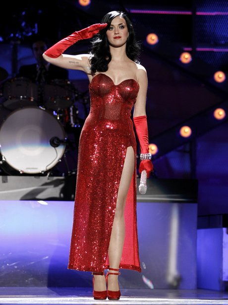 Katy Perry wearing a Jessica Rabbit red sequin dress on stage as she salutes the crowd