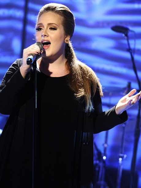 Adele singing on stage in a black dress