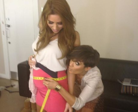 Frankie Sandford measures Una Healey's baby bump with a measuring tape