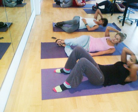 The Saturdays lie on gym mats and do sit ups