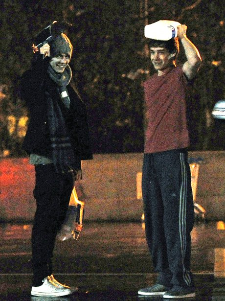 Harry and Liam form One Direction shelter from rain.