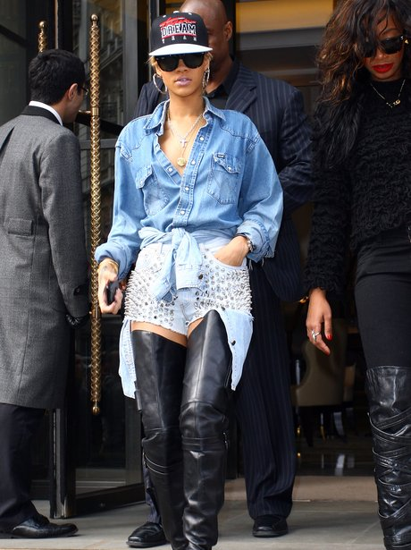 Rihanna in London weariing studded denim shorts and knee high leather boots