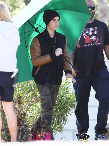 Justin Bieber holds and umbrella