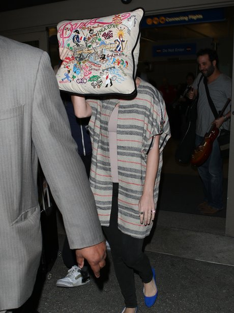 katy Perry hides behind a pillow at the airport