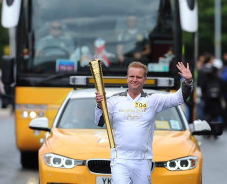 Smiles all round as torchbearer waves at the crowd