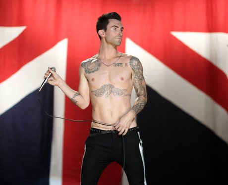 Adam Levine standing in front of a Union Jack flag