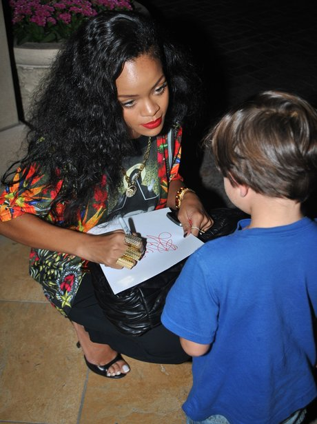 Rihanna signs an autograph for a young fan