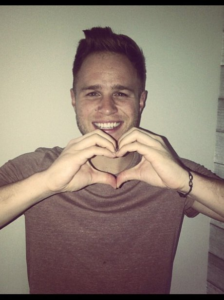 Olly Murs holds his hands in a heart symbol