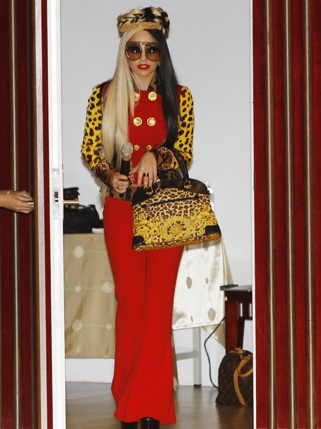 Lady Gaga wears red trouser suit.
