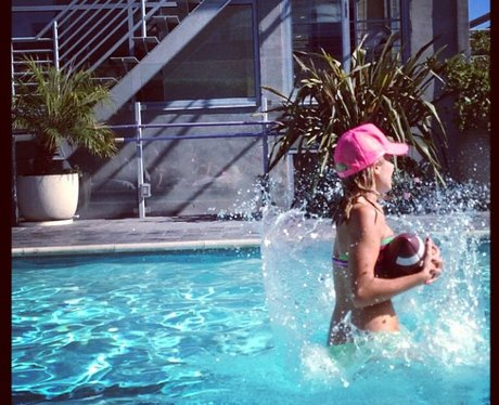 Mollie King playing American football in the pool