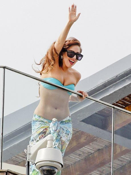 Lady Gaga waving at fans in a blue bikini
