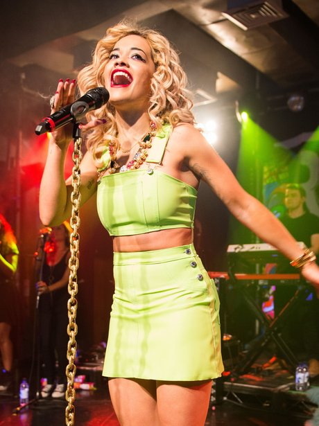 Rita Ora wearing a green dress on stage