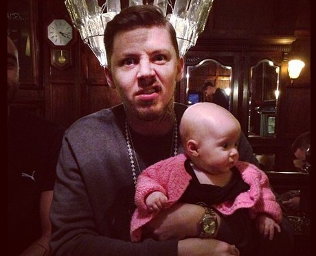 Professor Green holding a baby