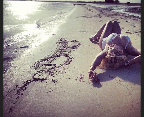 Rita Ora lying on a beach in a white swimsuit