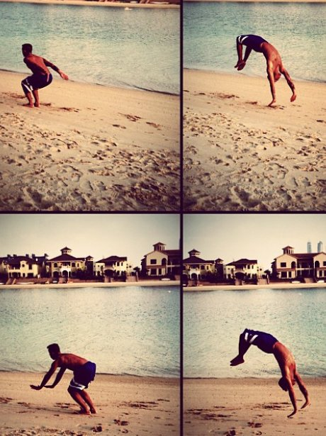 Aston Merrygold doing a back flip on the beach