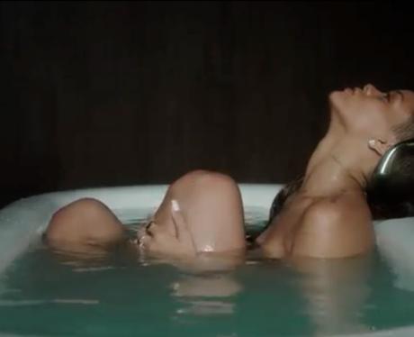 Rihanna reclining in a bath tub