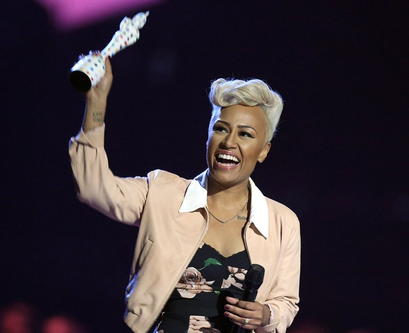 Emeli Sande holding BRIT Award in air On Stage