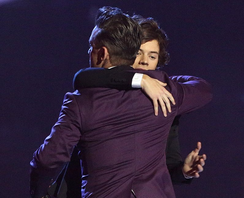 Harry Styles and Robbie Williams hug on stage at the BRITs
