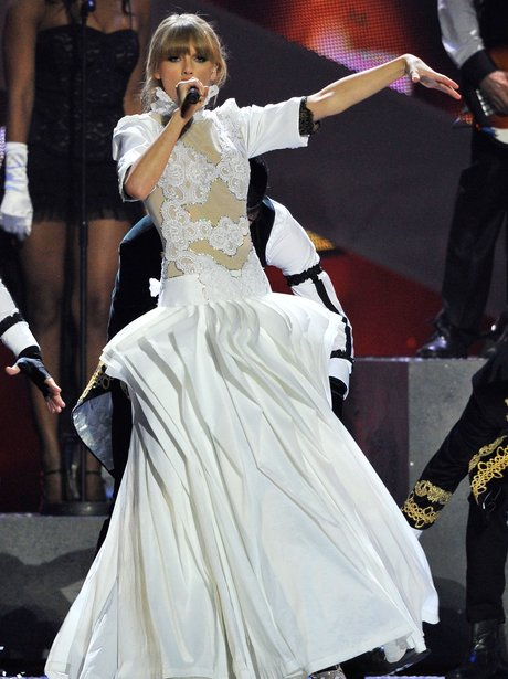 Taylor Swift wearing a white gown for her BRITs 2013 performance