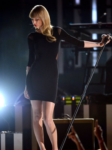 Taylor Swift performs onstage in tight black dress