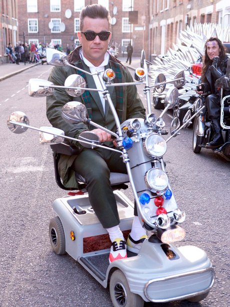 Robbie Williams sitting on a custom mobility scooter.