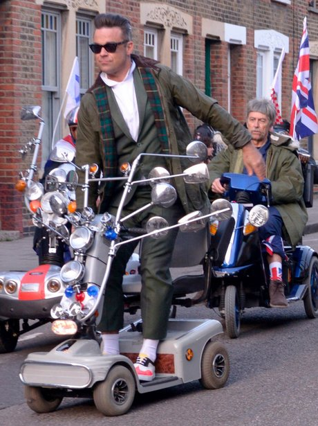 Robbie Williams stanidn up on Mobility Scooter wearing a green jacket and sunglasses
