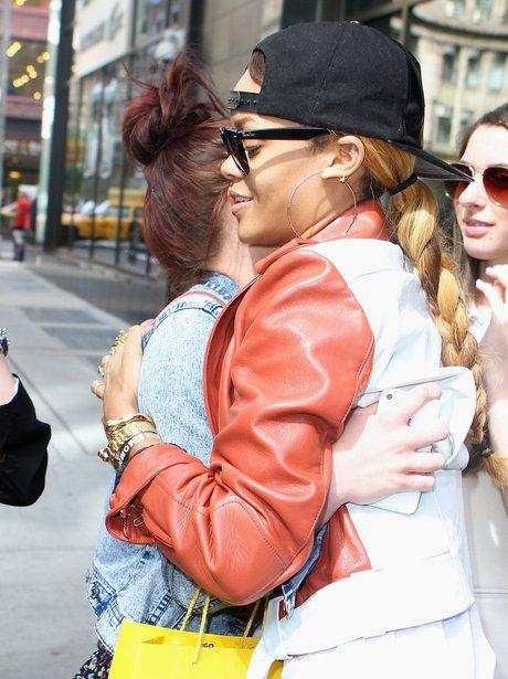 Rihanna hugging a fan in a black baseball cap