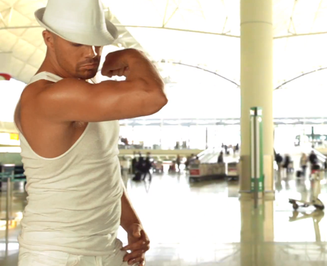 Max George flexing muscles in white vest