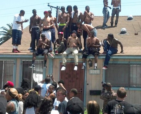 Chris Brown sitting on a roof filming Aaliyah video