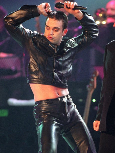 Robbie Williams wearing leather outfit with high heels
