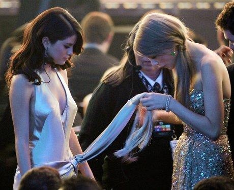 Taylor Swift holding Selena Gomez' dress