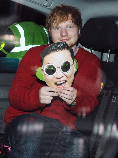 Ed Sheeran holds up a PSY mask after the Ball