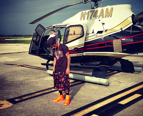 Justin Bieber stands next to a helicopter