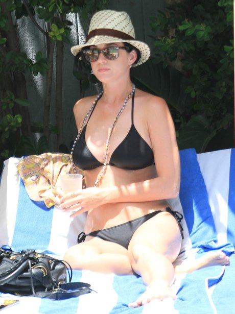 Katy Perry wearing a black bikini on a sun lounger