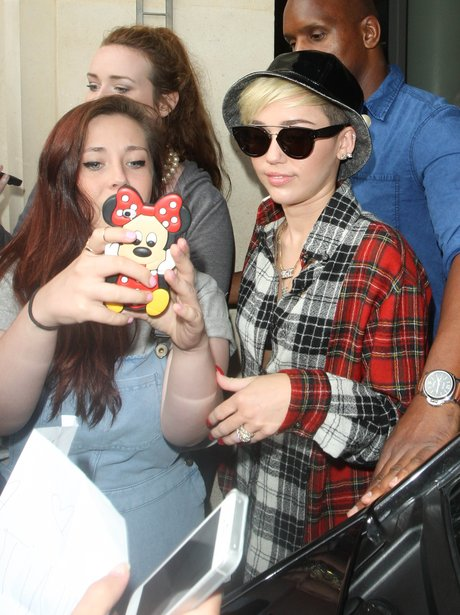 Miley Cyrus poses for a picture with a fan using a Minnie Mouse camera