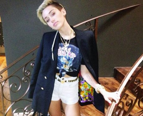 Miley Cyrus standing on a staircase in white hot pants