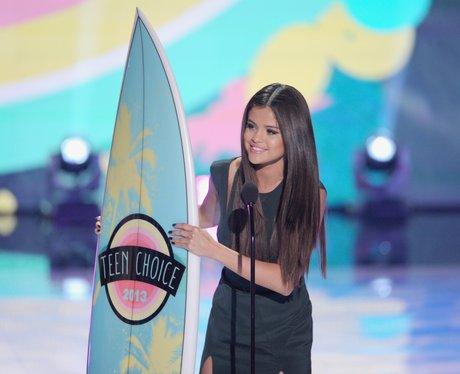 Selena Gomez holding Teen Choice Award surfboard in 2013