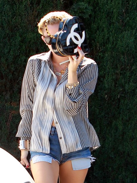 Miley Cyrus covers her face with a chanel handbag