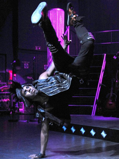 Jason Derulo performs a hand stand on stage