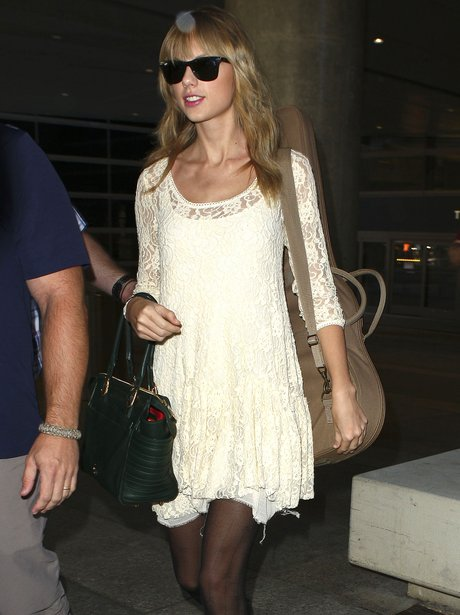 Taylor swift carrying her guitar at the airport